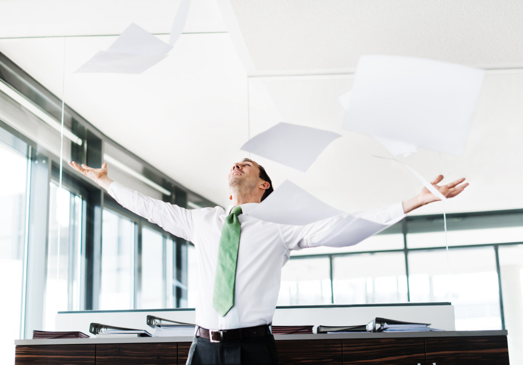Businessman Throwing Paper In Office