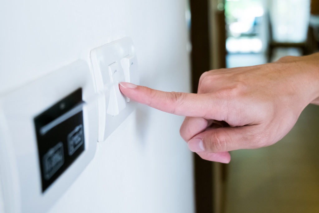 hand with finger on light switch, about to turn off the lights.