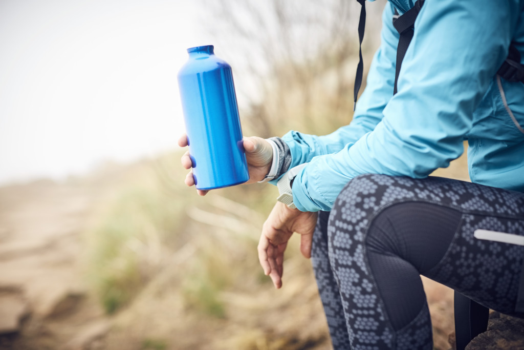 Midsection of female traveler holding water bottle